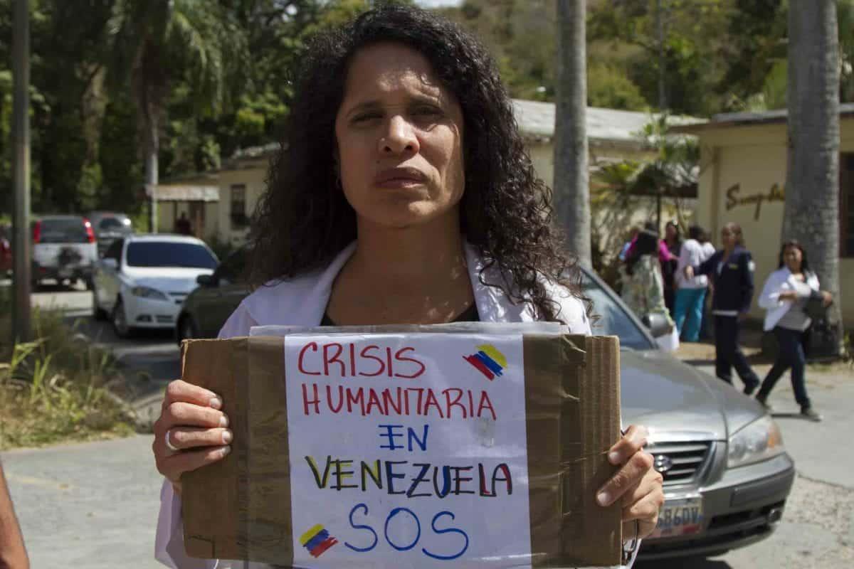 Mujer con cartel sobre emergencia humanitaria